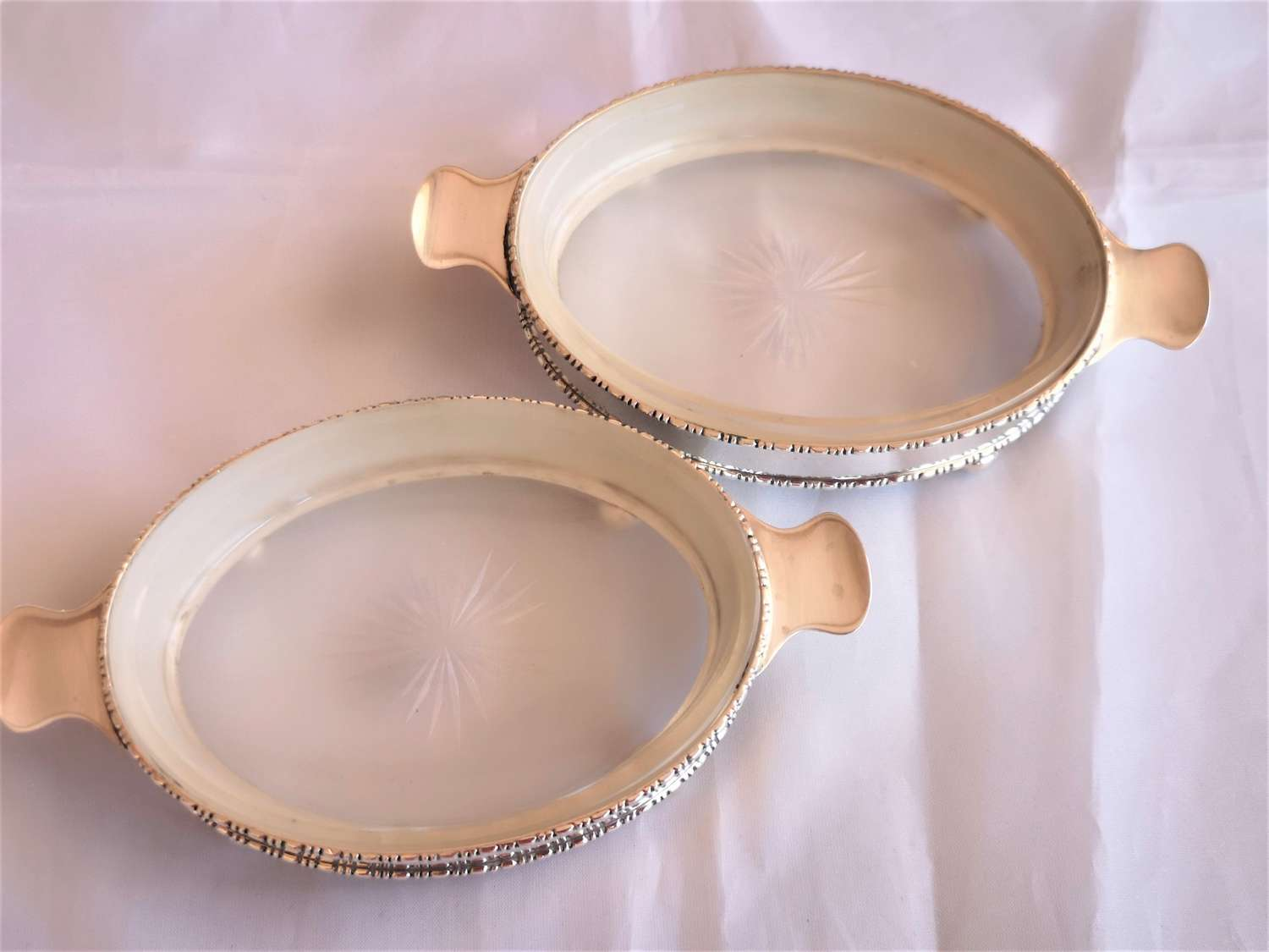 A pair of antique silver butter dishes